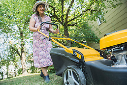 Senior woman mowing the lawn in a garden, Altoetting, Bavaria, Germany