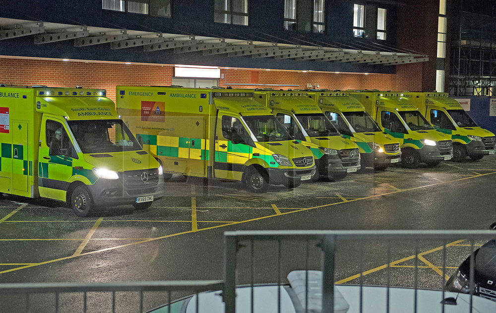 © Licensed to London News Pictures 07/01/2021.         Medway, UK. Ambulances waiting at the Accident and Emergency Department at Medway Maritime Hospital in Kent just before midnight tonight. Hospitals in the county of Kent are treating double the number of patients with Covid19 than in the first wave last year. Ambulance crews are having to wait for hours outside hosiptals with sick patients onboard. Photo credit:Grant Falvey/LNP