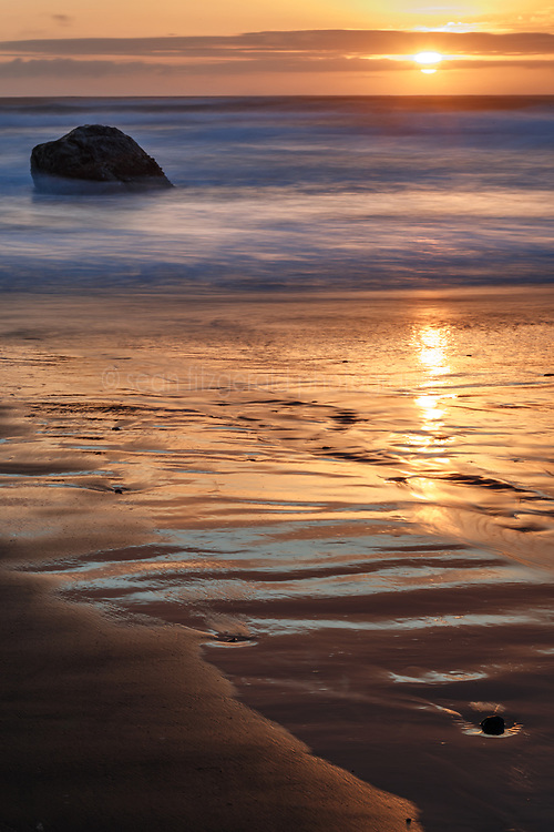 Beach and rock spires in Pacific Ocean at sunset, Hug Point State Recreation Area, Oregon, USA