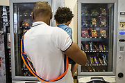 A young father  chooses something to eat from the vending machine  with his sone during a family visit in HMP Brixton, South London on the 26th of July 2016, London United Kingdom. The Prisoner Advice & Care Trust (PACT) organise special family days that help the men inside the prison connect with and support their partners and children on the outside. (photo by Andy Aitchison)