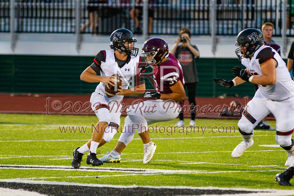 Norman's Isaac Raymond-Brown step back in the pocket to pass the ball as Edmond's Carson Mullins approaches to add pressure during the game in Edmond on Friday, October 05, 2018.
