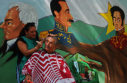 """Eileen Marquez, a member of the Bolivarian Circle, cuts the hair of Franklin Moreno in a plaza in downtown Caracas that is referred to as """"The Plaza of the Revolution"""".  The two are """"Chavistas"""", the name given to supporters of President Hugo Chavez. """"This is the begining of the changes that the country has always wanted"""" says Moreno.  In the background are images of famous figures in Venezuelan history, Francisco Miranda(left), Ezekiel Zamoro(middle) and Simon Bolivar."""