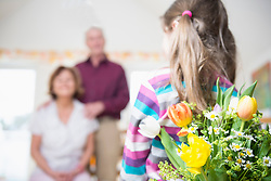 Granddaughter handover bouquet to her grandmother and grandfather in background
