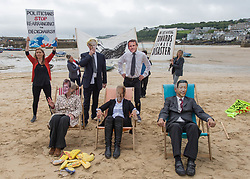 """© Licensed to London News Pictures.  11/06/2021. St Ives, UK. Members of the Extinction Rebellion environmental group perform """"Titanic"""" on Harbour Sand Beach in St Ives, Cornwall at the start of the G7 Summit. Photo credit: Marcin Nowak/LNP"""