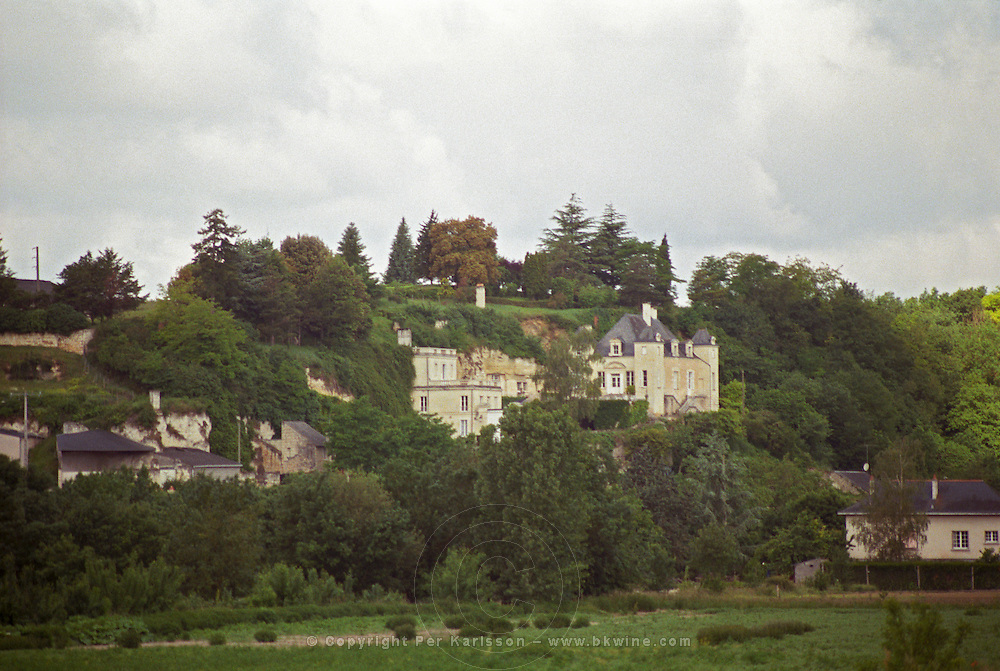 Chateau de Targe of Edouard Pisani in Saumur Champigny. The chateau is partially built in the rock using old lime stone quarry in troglodyte style under threatening rain clouds, Maine et Loire France