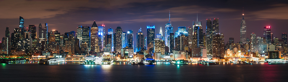 Times, Square, The Empire State Building, and the Chrysler Building are just a few landmarks of midtown Manhattan seen from the sweeping vistas of Old Glory Park across the Hudson River in Weehawken, NJ