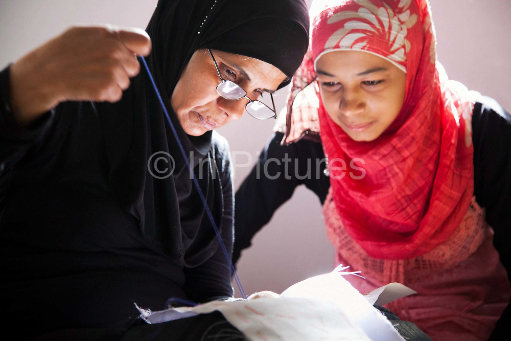 Delal shows a woman how to stitch.Delal is a Syrian Palestinian refugee from Damascus. She now lives in Shatila camp with her family after they fled the war in Syria. She runs workshops with her adult daughter where they teach other Syrian women refugees traditional handy craft.