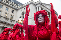 London, UK. 14 October, 2019. The Red Brigade join fellow climate activists from Extinction Rebellion staging theatrical mock trials, of the UK's financial sector for the crime of ecocide and of the Government for 'criminal negligence' in having permitted it, in front of the Bank of England. Roads were blocked around Bank on the eighth day of International Rebellion protests across London.
