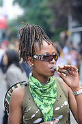 Notting Hill Carnival in West London. A celebration of West Indian / Caribbean culture and Europe's largest street party, festival and parade. Revellers come in their hundreds of thousands to have fun, dance, drink and let go in the brilliant atmosphere. A woman smoking a Cuban cigar.