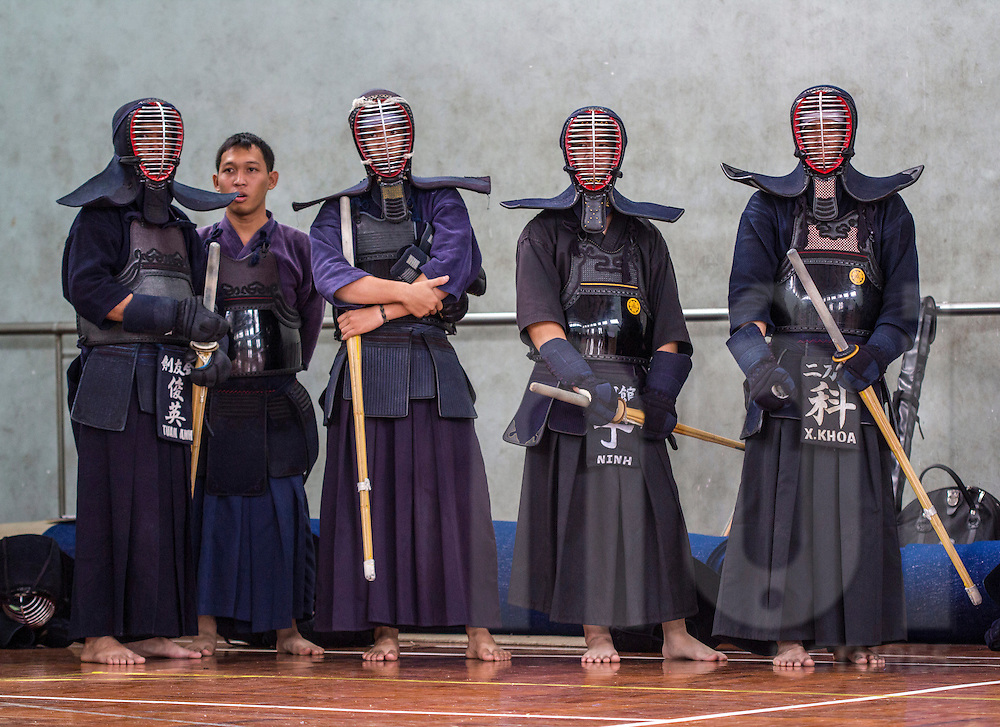 Vietnamese men wearing traditional Kendo martial art uniforms wait on the sideline for a fight, Vietnam, Southeast Asia