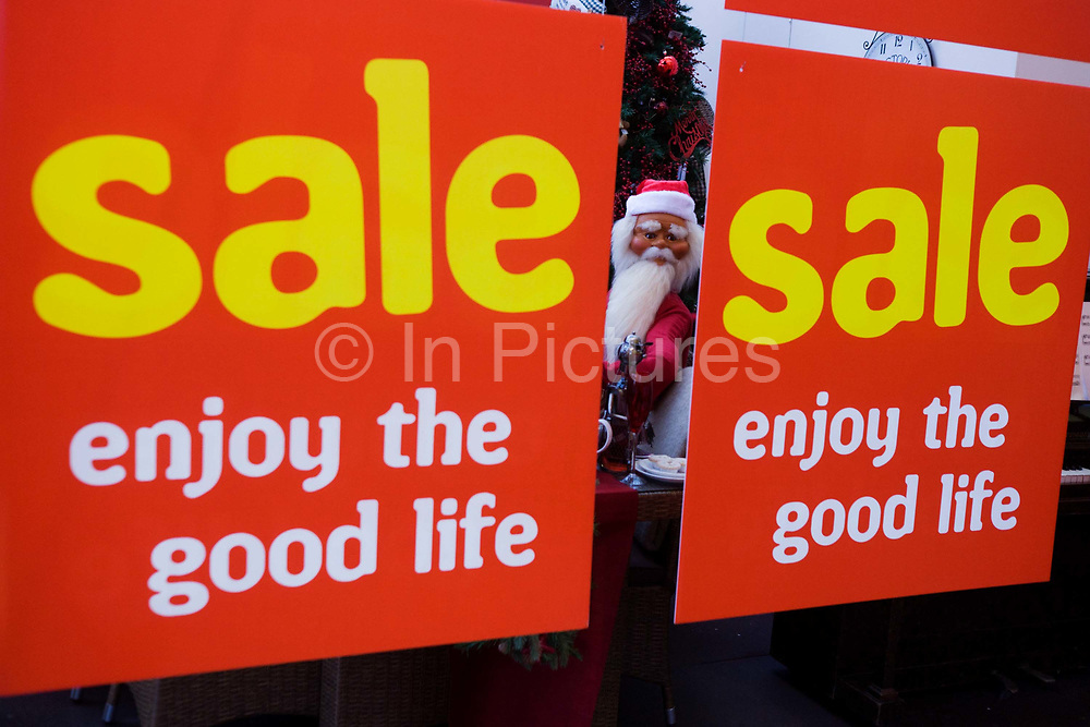 A mannequin of Santa Claus peers between Sale signs in garden retail centre in north Somerset, England. The inflated model is squeezed between the two red signs that tell shoppers to this rural shop to Enjoy the Good Life and that a Christmas sale is in force, the day after Boxing Day, the 27th December. Sale reductions and the lowering of prices are the lure for customers who need to beat the raising by the British Government of VAT (Value Added Tax) from 17.5 to 20% the following week - 4th January. Bargains will be offered at the old VAT rate making this the most popular of the holiday period to save during economic hardship.