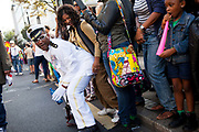 Hackney carnival 2014. The procession started in Ridley Road and passed by the The Hackney Town Hall with thousands of spectators lining the road. A white uniformed male dancer grind with a spectator while he passes the Town Hall.