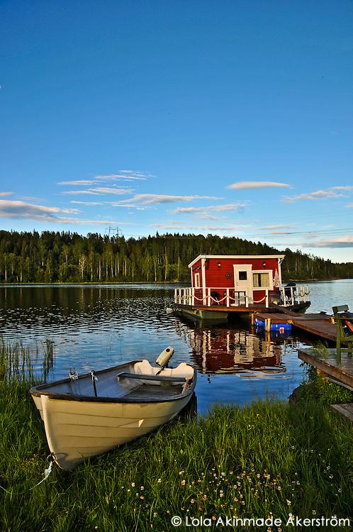 Floating stuga (cottage) and rowboat in Northern Sweden