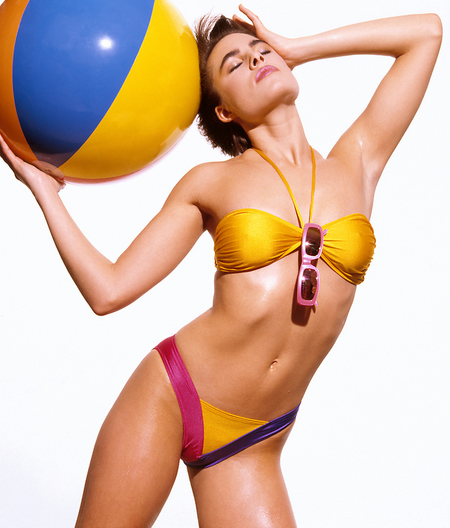 Happy woman in colorful bikini holding multicolored beachball in front of white background
