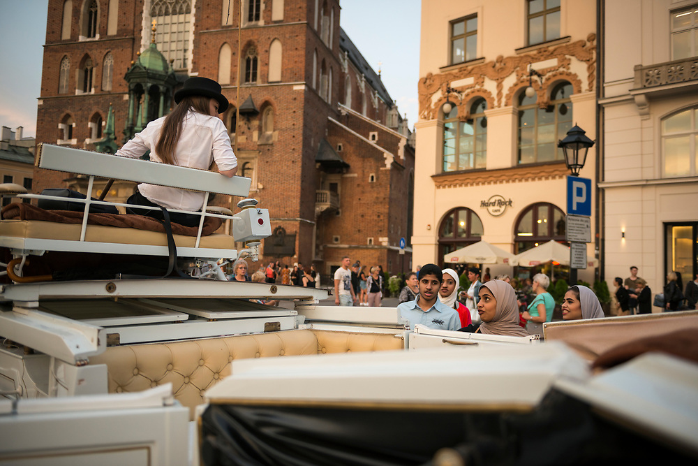 Krakow, Poland - September 2, 2016: A Polish carriage driver in Krakow's Rynek Glowny Square talks to a group of Arab tourists interested in paying for a horse-drawn carriage ride.