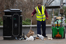© Licensed to London News Pictures. 01/04/2021. London, UK. A worker clears rubbish from around a bin in Cutty Sark Gardens after large groups of people visited to enjoy the warm weather and take advantage of new lockdown rules that allow groups of six to meet outside. Photo credit: George Cracknell Wright/LNP