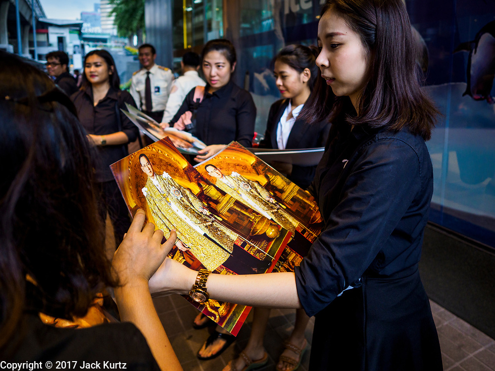 26 OCTOBER 2017 - BANGKOK, THAILAND: People hand out portraits of Bhumibol Adulyadej, the Late King of Thailand, in front of a Bangkok shopping mall  during the funeral ceremony for Bhumibol Adulyadej, the Late King of Thailand. The king died on 13 October 2016 and was cremated 26 October 2017, after a mourning period of just over one year. The revered monarch was the longest reigning king in Thai history and is credited with guiding Thailand through the turbulent latter half of the 20th century.       PHOTO BY JACK KURTZ