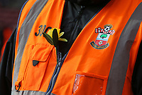 Football - 2018 / 2019 Premier League - Southampton vs. Cardiff City<br /> <br /> A Southampton steward wares a Daffodil in tribute to in tribute to Emiliano Sala at St Mary's Stadium Southampton<br /> <br /> COLORSPORT/SHAUN BOGGUST