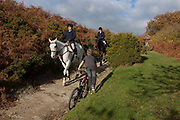 Members of a local hunt ride their horses on a hillside bridle path on the Welsh/English border between Gladestry and Kington. Riders ontheir horses make their way down a footpath/bridleway from the 426 metres high Hergest Ridge towards Gladestry in Wales. A young boy pushes his bike up the hill as the horses pass. The ridge inspired an album by English multi-instrumentalist Mike Oldfield, Hergest Ridge: So if you feel a little glum, to Hergest Ridge you should come. In summer, winter, rain or sun, its good to be on horseback.