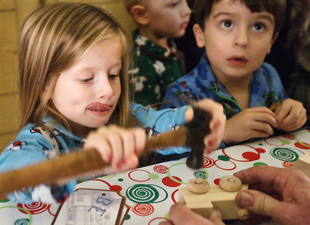 Dakin Geiser of Grand Island works to put together a toy train with her 4-year-old twin brother Isaac during the North Pole Express event Saturday at the Stuhr Museum.  (Independent/Matt Dixon)