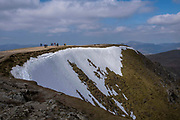 Groups of people walking along the plateau path towards the summit of Helvellyn Mountain, Lake District, Cumbria, UK. It is a bright, sunny day, but there is snow on the mountain side. Helvellyn is the third-highest point in England and is located in the beautiful Lake District National Park and part of the Eastern Fells.