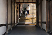 couple going up a long stairway at the end of a corridor Japan Nara at the Todai-ji Nigatsu-do Temple