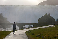 © Licensed to London News Pictures. 16/02/2020.  Rhayader, Powys, Wales, UK. A woman visits the Caban Coch reservoir as raging torrents of water cascade over the Caban Coch  dam in Elan valley after extremely heavy rainfall in Powys yesterday, last night and today. Photo credit: Graham M. Lawrence/LNP