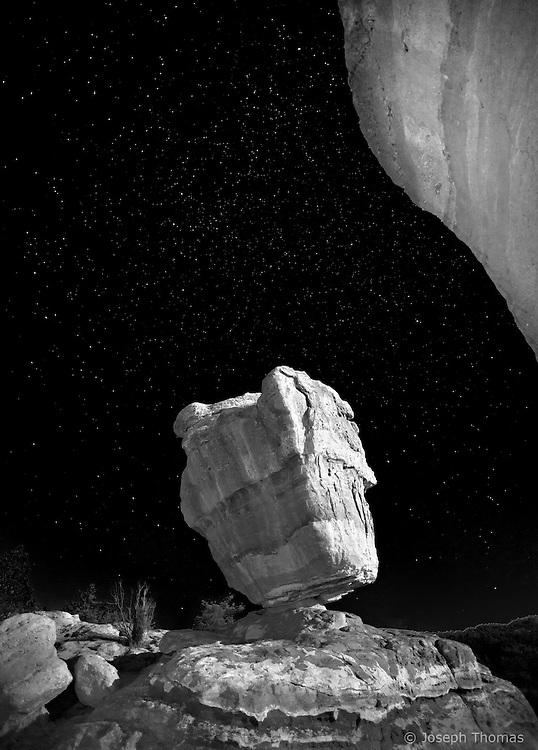 The rising full moon illuminates a gravity defying formation.