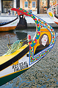 Traditional brightly painted gondola style moliceiro canal boat with painted prow in Aveiro, Portugal