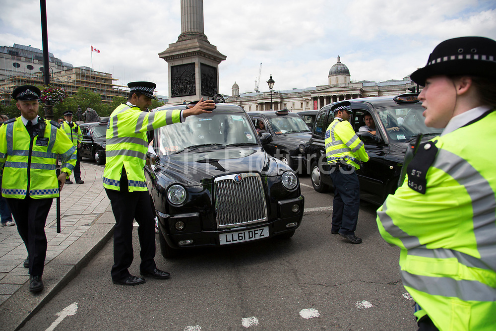 London, UK. Wednesday 11th June 2014. Black taxi drivers protest against taxi service app Uber, brings central London to a standstill, blocking Trafalgar Square. Joined in many numbers by future black cab drivers on mopeds currently doing 'The Knowledge'. London cabbies emphasised that they had no problem with Uber, only with Transport for London for not enforcing current legislation. Taxi drivers say the Uber app is tantamount to a meter and should be regulated like taxi meters. Uber says it has seen an 850% increase in sign-ups compared to last Wednesday and describes the London Taxi Drivers Association (LTDA), as being stuck in the dark ages.