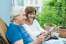 Couple using digital tablet, smiling