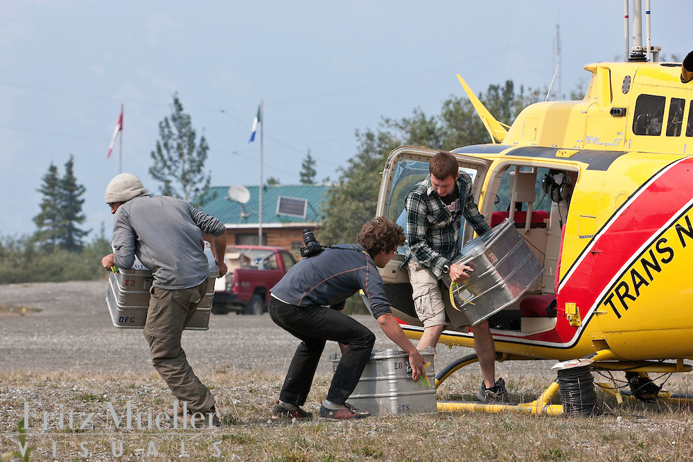 Researchers unload equipment from a helicopter returning from a glaciology field camp in the icefields of Kluane National Park, Yukon