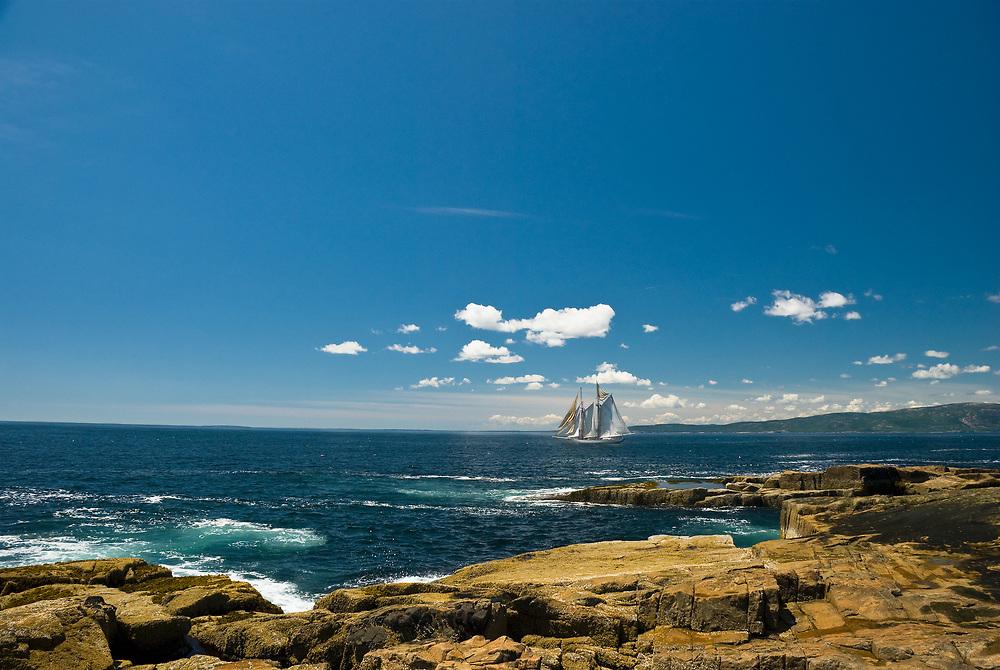 A schooner, one of many in the area, is shown here off the Schoodic Peninsula, with the archipelago of islands south of Acadia National Park, Maine, in the distance under cumulus clouds.
