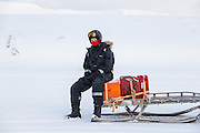Glaciologist Poul Christoffersen waits seated on a snowmobile sled in Sassendalen, Svalbard on a UNIS class field trip to Tunabreen.