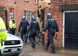 © Licensed to London News Pictures; 10/03/2021; Bristol, UK. Police and bailiffs at the scene try to evict a squatted building on Gloucester Road in North Bristol. The squatters say they are called The Pigeon Shit Collective, because of the Government's failings, and they are giving support to homeless people and those in need during the covid-19 coronavirus pandemic. Photo credit: Simon Chapman/LNP.