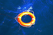 Orange life buoy with rope in the water
