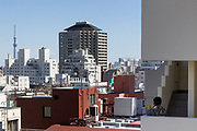 A jJapanese woamn talk on her cellphone on stair at the back of a buiding in Myogadani, with Tokyo Skytree behind her on the horizon. Tokyo, Japan. Wednesday March 11th 2020