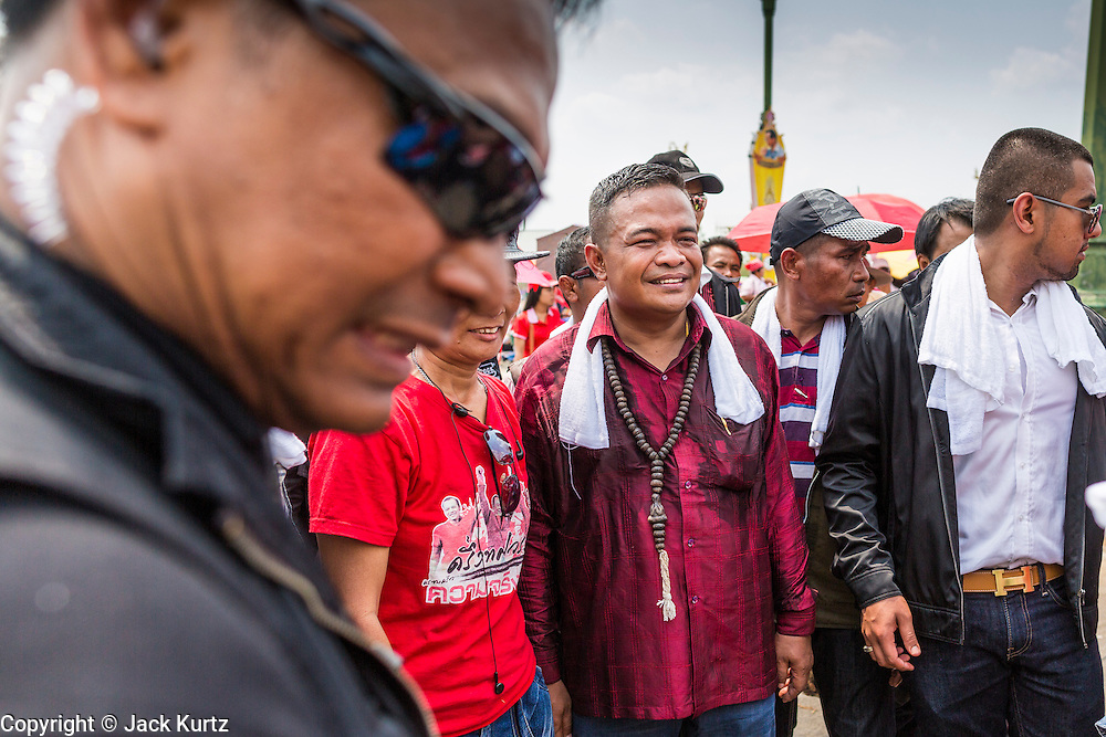 06 APRIL 2014 - BANGKOK, THAILAND: A bodyguard, left, frames JUTAPORN PROMPAN, the leader of the Red Shirts as they walk through a crowd at the Red Shirt rally in Bangkok Sunday. Red Shirts and supporters of the government of Yingluck Shinawatra, the Prime Minister of Thailand, gathered in a suburb of Bangkok this weekend to show support for the government. The Thai government is dealing with ongoing protests led by anti-government activists. Legal challenges filed by critics of the government could bring the government down as soon as the end of April. The Red Shirt rally this weekend was to show support for the government, which public opinion polls show still has the support of most of the electorate.   PHOTO BY JACK KURTZ