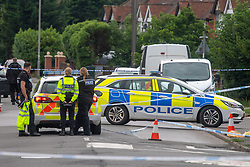 CAPTION UPDATE © Licensed to London News Pictures. 31/07/2021. High Wycombe, UK. Police vehicles form a cordon on Micklefield Road as a murder investigation is launched in High Wycombe following the discovery by a police patrol of a person on the ground at approximately 12:20BST surrounded by a group of males who fled the scene when the police officers arrived, despite the efforts of police and paramedics the man died at the scene. Photo credit: Peter Manning/LNP