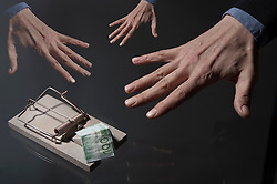 Businessman's hands reaching for money in mousetrap, Bavaria, Germany