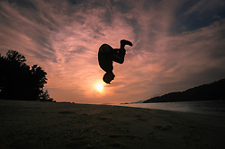 boy making backward roll at sunset, Koh Lipe, Thailand