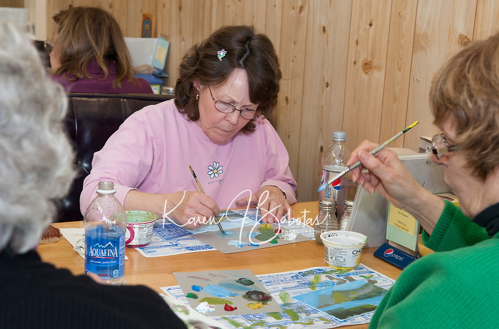 Jennifer Muzzey mixes paint on her color palette with her fellow artists Sharyn Childs and Lois Philbrick during Larry Frates painting class held at the Vintage Cafe in downtown Laconia on Saturday afternoon.  (Karen Bobotas/for the Laconia Daily Sun)