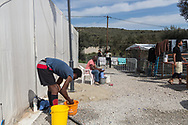 Men wash themselves in the makeshift settlement next to the official Moria refugee camp site is home to an estimated 1500 asylum seekers. Scattered amongst the olive groves, people live in tents and shelters in this unofficial site.
