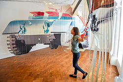 "© Licensed to London News Pictures. 10/09/2019. LONDON, UK. A staff member views ""Forest Ranger"", 1967, at a preview of ""Visualising the Sixties"", the first in depth exhibition of works by artist James Rosenquist.  From a painter of commercial billboards in New York City, to a fine art career as a Pop artist, Rosenquist's work was described as Andy Warhol's favourite.  The exhibition is on at Galerie Thaddaeus Ropac in Mayfair 10 September to 9 November.  Photo credit: Stephen Chung/LNP"
