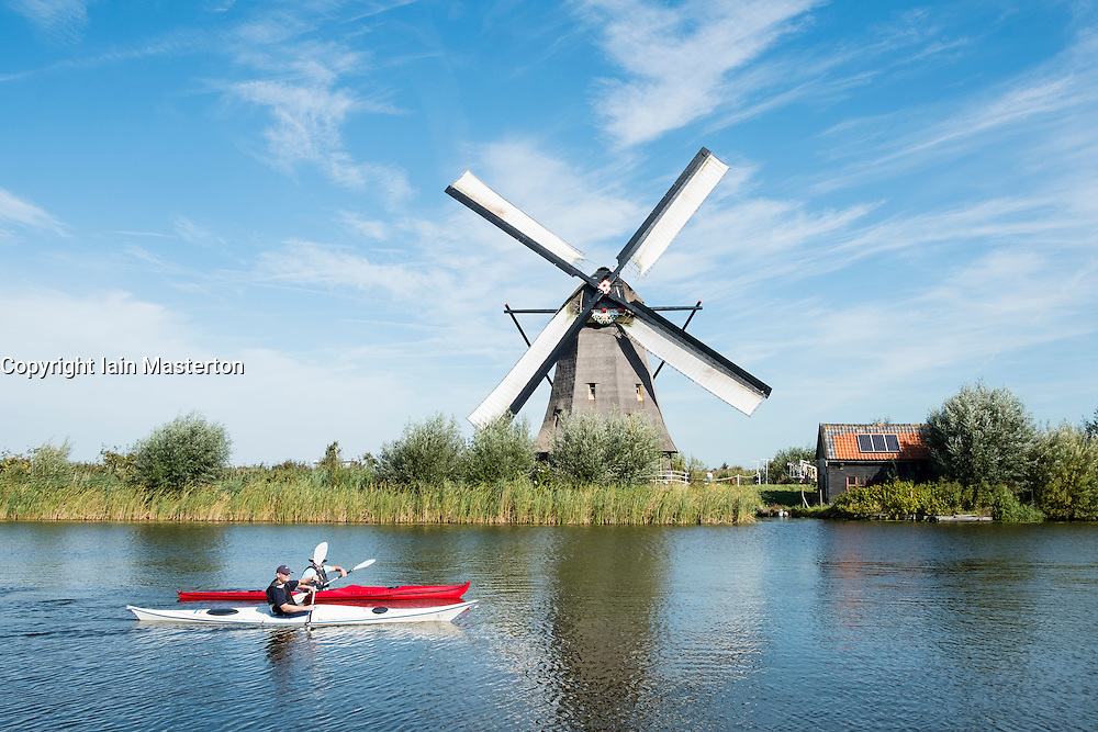 Two men in kayaks in canal in front of historic windmills at Kinderdijk UNESCO World Heritage Site in The Netherlands