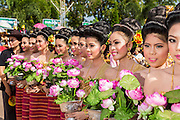 28 JUNE 2014 - DAN SAI, LOEI, THAILAND: Women in Dan Sai line up before the ghost festival parade. Phi Ta Khon (also spelled Pee Ta Khon) is the Ghost Festival. Over three days, the town's residents invite protection from Phra U-pakut, the spirit that lives in the Mun River, which runs through Dan Sai. People in the town and surrounding villages wear costumes made of patchwork and ornate masks and are thought be ghosts who were awoken from the dead when Vessantra Jataka (one of the Buddhas) came out of the forest.    PHOTO BY JACK KURTZ