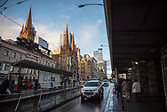 Pedestrian and vehicle traffic outside Flinders Street Station in the Central Business District of Melbourne, Victoria. The church on the left is St. Paul's Cathedral.