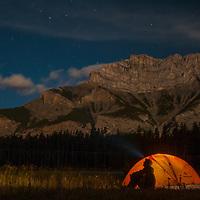 Sitting below Cascade Mountain, a camper admires moonlit scenes in Banff National Park, Alberta, Canada.