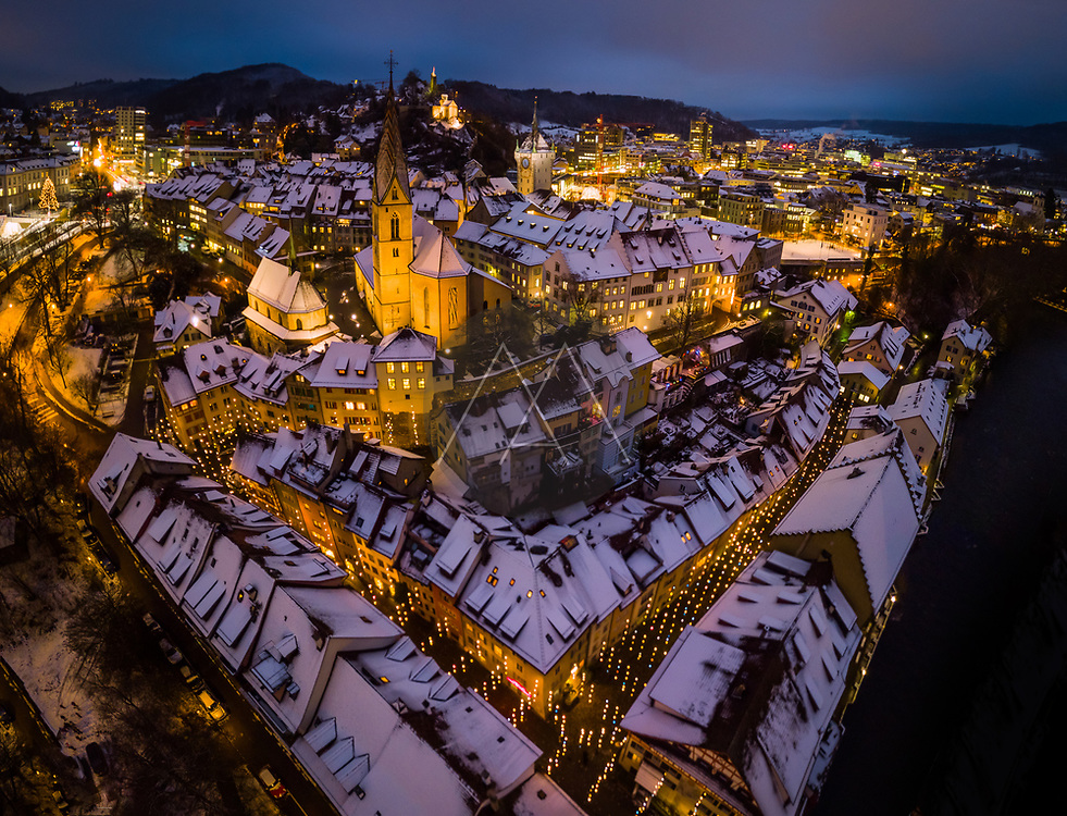 Aerial view of snow-capped roofs of historic town of Baden, Switzerland, with colorful christmas lights lighting the streets