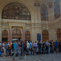 Illegal migrants queue to buy tickets for their train to travel to Germany at the main railway station Keleti in Budapest, Hungary on August 31, 2015. ATTILA VOLGYI